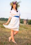 Eine junge Frau in einem langen Weiß stickte Hemd und in einem Kranz Lizenzfreies Stockfoto