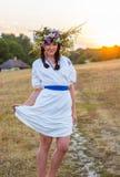 Eine junge Frau in einem langen Weiß stickte Hemd und in einem Kranz Stockbild
