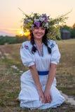 Eine junge Frau in einem langen Weiß stickte Hemd und in einem Kranz Lizenzfreie Stockfotos