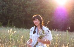 Eine junge Frau in einem langes Weiß gestickten Hemd erfasst Blumen Stockfotos