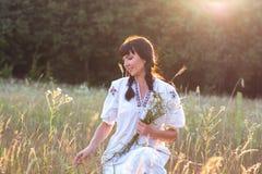 Eine junge Frau in einem langes Weiß gestickten Hemd erfasst Blumen Stockfotografie