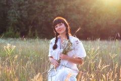 Eine junge Frau in einem langes Weiß gestickten Hemd erfasst Blumen Lizenzfreies Stockfoto