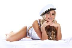 Eine junge Frau in einem Seemannhut legt auf ein Bett Stockfotos