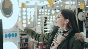 Eine junge Frau in einem Speicher von Elektrogeräten und von Lampen Die Dame wählt Einzelteile für den Innenraum ihres Hauses, Ha stock footage