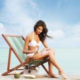Eine junge Frau in einem weißen Badeanzug, der Sonnencreme hinzufügt Stockfotos