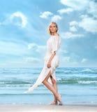 Eine junge Frau in einem weißen Kleid auf einem Strandhintergrund Stockbilder