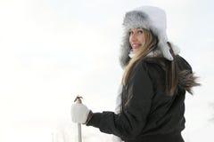 Eine junge Frau in einem Winterkleid-Holdingski haftet Lizenzfreies Stockfoto