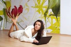 Eine junge Frau in einer weißen Robe mit Laptop Lizenzfreies Stockbild