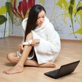 Eine junge Frau in einer weißen Robe mit Laptop Lizenzfreie Stockbilder
