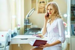 Eine junge Frau in einer weißen Robe um das Telefon im Büro eines Kosmetikers ersuchend lizenzfreies stockbild