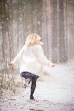 Eine junge Frau in einer weißen warmen Wolljacke, die in einen Wald läuft und ein Bündel erste Frühlingsblaublumen hält Stockfotografie