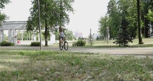 Eine junge Frau fährt in den Park rad stock video footage