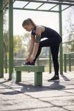 Eine junge Frau, Freienpark, Sportkleidung, Spitzee binden lizenzfreies stockbild
