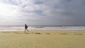Eine junge Frau geht auf den Ozean Nordstrand in Nazare, Portugal stock video