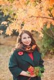Eine junge Frau geht in den Herbst Park Brunettefrau, die einen grünen Mantel trägt stockbild