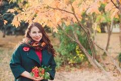 Eine junge Frau geht in den Herbst Park Brunettefrau, die einen grünen Mantel trägt Sie hält einen Blumenstrauß von gelben Blätte stockfotos