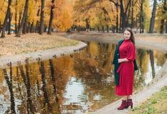 Eine junge Frau geht in den Herbst Park Brunettefrau, die einen grünen Mantel und ein rotes Kleid trägt stockbild