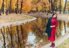 Eine junge Frau geht in den Herbst Park Brunettefrau, die einen grünen Mantel und ein rotes Kleid trägt lizenzfreies stockbild