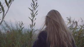 Eine junge Frau geht gegen den Hintergrund des Sees unter sehr hohem grünem Gras stock footage