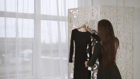 Eine junge Frau geht oben zu einem Schirm, an dem ein Kleid an einem Aufhänger hängt stock video footage