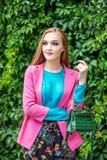 Eine junge Frau geht um die Stadt Rosafarbene Jacke Das Konzept von lizenzfreies stockbild