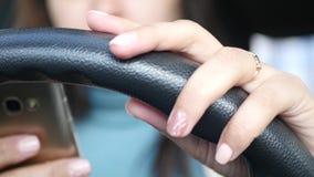 Eine junge Frau hält ein Auto mit einer Hand, die andere betrachtet etwas im Telefon 4K 30FPS 3840x2160 stock footage