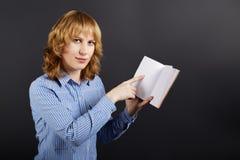 Eine junge Frau hält ein Notizbuch in einer Hand und Punkte zu ihr mit Lizenzfreie Stockbilder