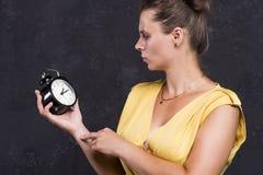 Eine junge Frau hält eine Uhr Setzen Sie Zeit Konzeptes fest Wenden Sie getrennt auf weißem Hintergrund ein lizenzfreie stockbilder