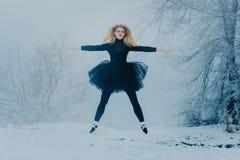 Eine junge Frau im schwarzen Bündel im Winter lizenzfreies stockfoto