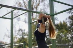 Eine junge Frau, 20-29 Jahre, Profilansicht, ihr Haar im Pferdeschwanz binden, draußen lizenzfreie stockbilder