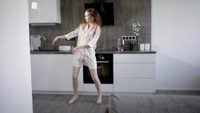 Eine junge Frau kleidete in den Pyjamas täuscht herum während des Tanzes, die Dame springt aktiv um die Küche an stock footage