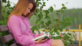 Eine junge Frau liest ein Buch beim Sitzen auf einer Parkbank stock video footage