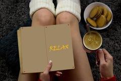Eine junge Frau liest ein Buch, trinkenden Kaffee und isst Kekse Stockbilder