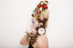 Eine junge Frau mit Blumen auf ihrem Kopf und Händen Frühlingsbild mit Blumen Mann mit einer bunten Anlage Das Mädchen und das Bl Lizenzfreies Stockfoto