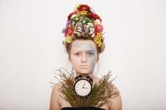 Eine junge Frau mit Blumen auf ihrem Kopf und Händen Frühlingsbild mit Blumen Mann mit einer bunten Anlage Das Mädchen und das Bl Lizenzfreie Stockbilder