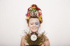 Eine junge Frau mit Blumen auf ihrem Kopf und Händen Frühlingsbild mit Blumen Mann mit einer bunten Anlage Das Mädchen und das Bl Stockfotografie