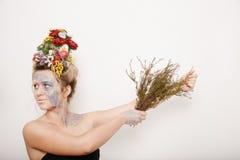 Eine junge Frau mit Blumen auf ihrem Kopf und Händen Frühlingsbild mit Blumen Mann mit einer bunten Anlage Das Mädchen und das Bl Lizenzfreie Stockfotos