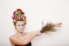 Eine junge Frau mit Blumen auf ihrem Kopf und Händen Frühlingsbild mit Blumen Mann mit einer bunten Anlage Das Mädchen und das Bl Lizenzfreies Stockbild