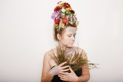 Eine junge Frau mit Blumen auf ihrem Kopf und Händen Frühlingsbild mit Blumen Mann mit einer bunten Anlage Das Mädchen und das Bl Stockfoto