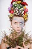 Eine junge Frau mit Blumen auf ihrem Kopf und Händen Frühlingsbild mit Blumen Mann mit einer bunten Anlage Das Mädchen und das Bl Stockbilder