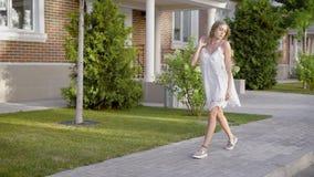 Eine junge Frau mit dem blonden Haar, das in einem weißen Designerkleid geht gekleidet wird elegant, hinunter die Straße tagsüber stock video footage