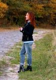 Eine junge Frau mit dem roten Haar steht auf dem Weg in einer schwarzen Jacke und hält das Telefon in ihrer Hand Warten auf einen stockbilder