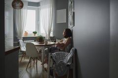 Eine junge Frau mit einem Baby, das heraus in einer gemütlichen grauen Küche und in den Blicken das Fenster sitzt Lizenzfreies Stockbild