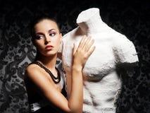 Eine junge Frau mit einem Mannequin auf einem Weinlesehintergrund Stockfotos