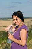 Eine junge Frau mit einer Flasche Wasser. Stockfotografie