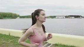 Eine junge Frau mit einer schlanken Zahl, die das Laufen beginnt Zeitlupekamera stock footage