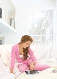 Eine junge Frau mit einer Tablette im modernen Innenraum stockbild
