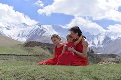 Eine junge Frau mit zwei T?chtern in den roten Kleidern, die im Fr?hjahr in den Schnee-mit einer Kappe bedeckten Bergen stillsteh stockfotografie