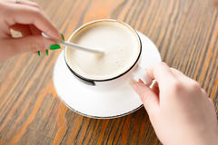 Eine junge Frau rührt den Kaffee lizenzfreies stockbild