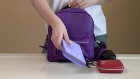 Eine junge Frau sammelt ihre Tasche, bevor sie erlischt Inhalt der Damentasche stock footage